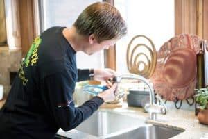 shamrock plumber working in faucet
