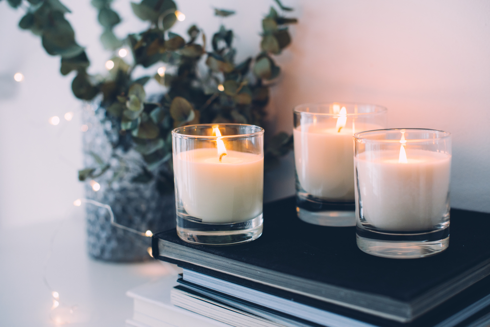 lit candles sitting on a fireplace mantel