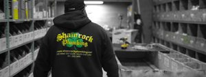 The logo of a Utah business, Shamrock Plumbing, on the back of a black hoodie.