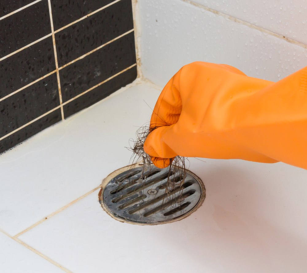 orange glove and shower drain